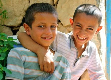 Two young Iraqi boys smile and pose for a photo, with one placing his harm around the other.
