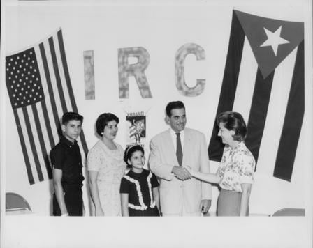 "A Cuban family of four poses with an IRC staff member in front of a wall that says ""IRC,"" next to a Cuban flag and a U.S. flag."