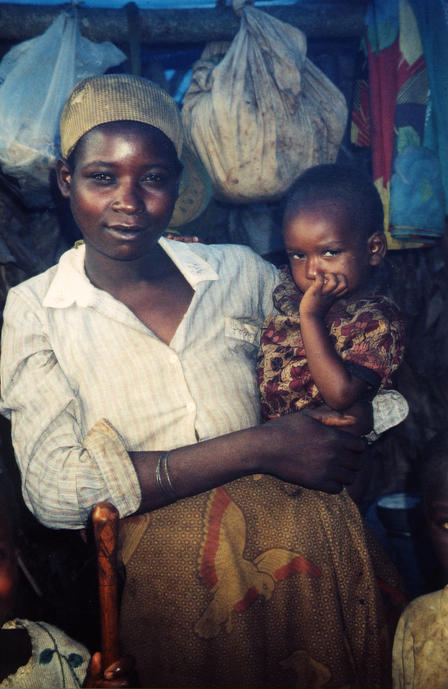 An Angolan woman stands and holds a small child as they look at the camera.
