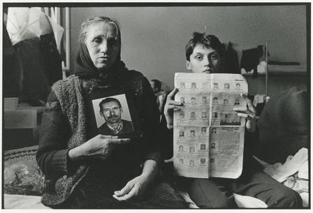 A woman and a young boy sit next to each other on a bed, holding up photos of the faces of men killed in conflict.