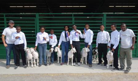 Goat Project 4-H Youth present ribbons won standing with goats