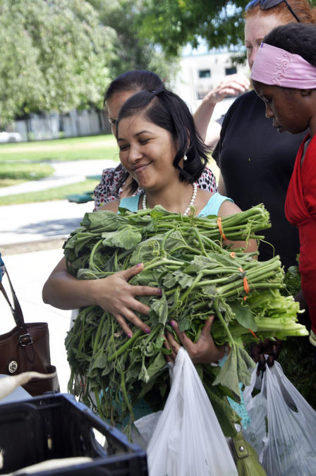 Woman purchases produce at the Sunnyvale Farmers Market outdoors