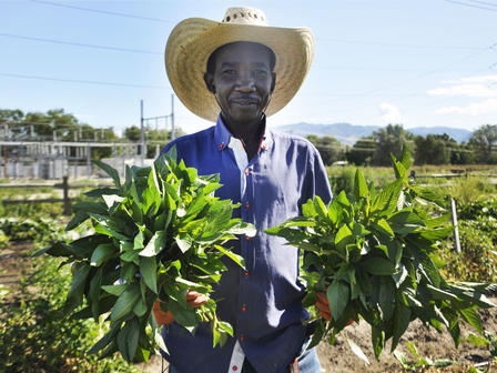 Man in sunhat holds produce grown at New Roots Farm