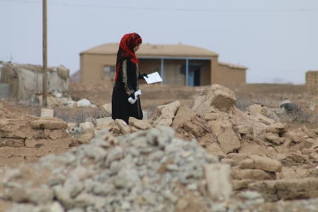A Syrians displaced woman walks through rubble