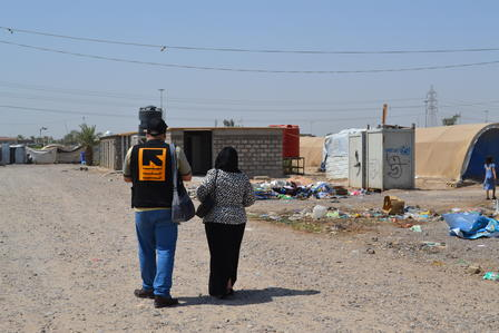 Community representatives walk through the camp