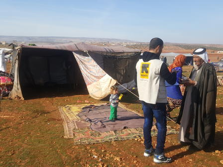 An IRC aid worker speaks with a man whose family has been displaced in Syrias Idlib province