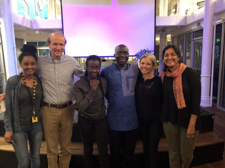 Daniel Oduntan, an entrepreneur with the International Rescue Committee's Microbusiness Connection Center, stands with IRC staff and family members at the New American Dream Lab event.