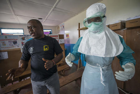 During the 2014 Ebola outbreak in West Africa, the IRC trained local health workers in how to use personal protective equipment when treating Ebola patients.