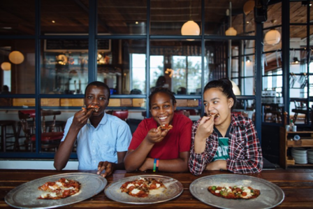 From left: Moise, Mariam and Pay Pay enjoy the pizza they made at Eno's Pizza Tavern as part of the Youth Food Justice Internship