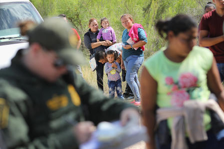 Central American asylum seekers wait as U.S. Border Patrol agents take groups of them into custody near McAllen, Texas.