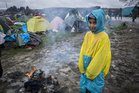 A Syrian girl in a raincoat stands by a campfire in a refugee settlement in Greece