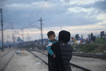 A refugee women holds a small boy in a refugee settlement in Greece.