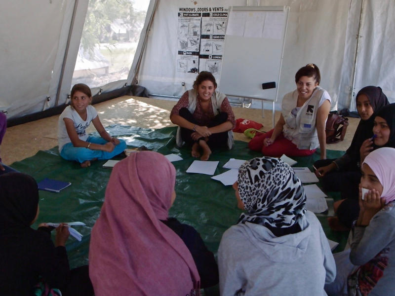 """Girls sit in a circle playing a game in a tent that serves as an IRC """"safe space"""" in a refugee camp in Greece."""