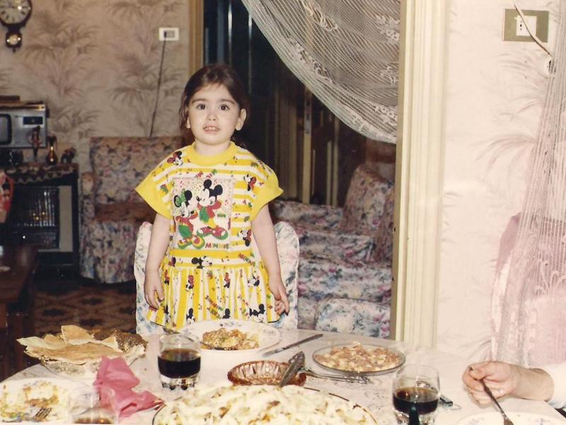 Dressed in festive clothing, Mariela stands at a table filled with edible treats