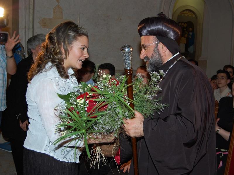 Mariela Shaker, with flowers, greets Syriac-Orthodox archbishop Mar Gregorios Yohanna Ibrahim.