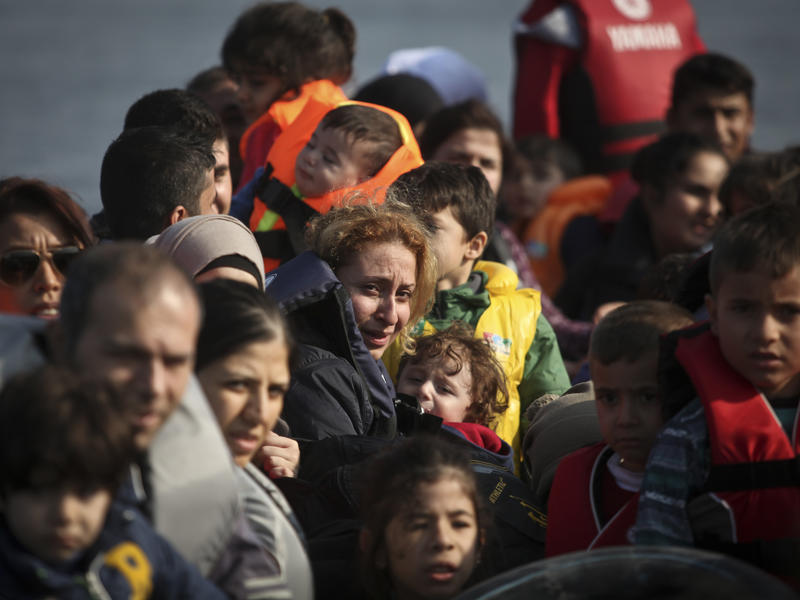 Syrian refugees, including women and children,  approach the shores of Lesbos, Greece in an overcrowded rubber raft.