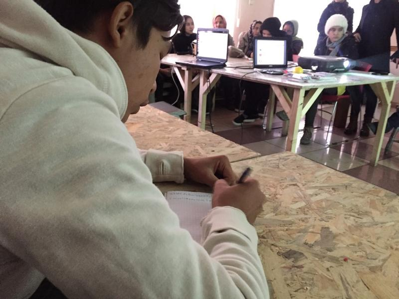 A boy writes an assignment at his desk in an English class for refugee children in Belgrade.