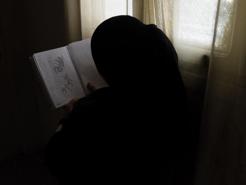 Rawan holds a notebook filled with her writing