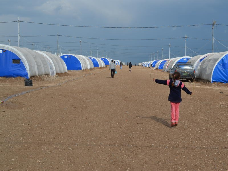 Children play among rows of tents set on sandy soil in Nargilzila camp.