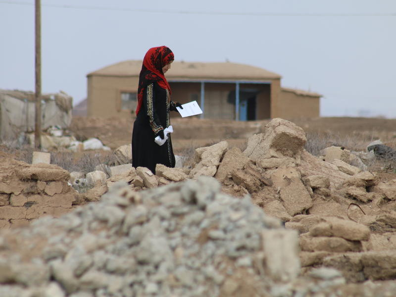 A woman picks her way through rubble in a village in rural, northeastern Syria that has been heavily damaged during the war.