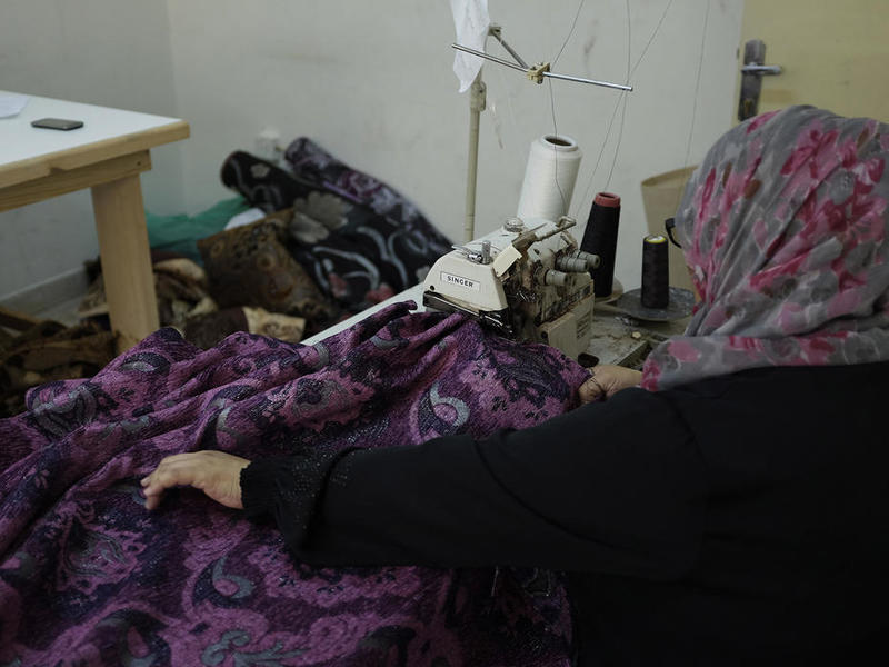 A woman works at a sewing machine at her family's newly restarted upholstery business in Jordan