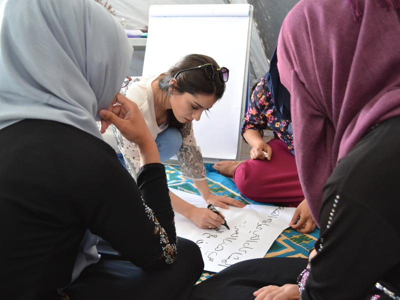 The IRC's Zaytoon Saeed writes on a poster as she leads teenage girls in a negotiation skills activity at the IRC's women's center.