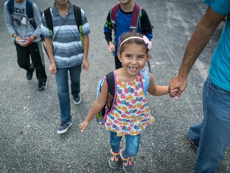 5-year-old Jori walks to school holding her father's hand