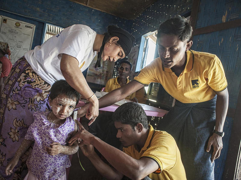 IRC health workers examine a child in a medical clinic in Rakhine State