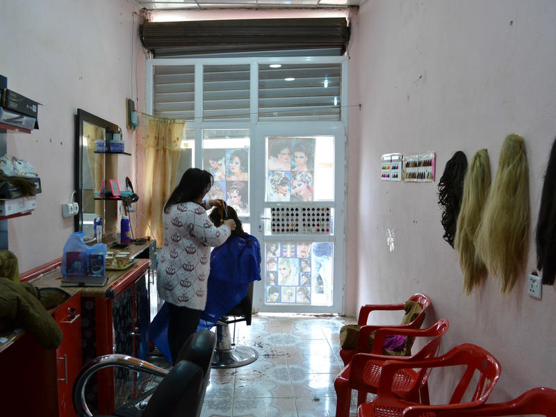 Hadeel styles a customer's hair in her salon