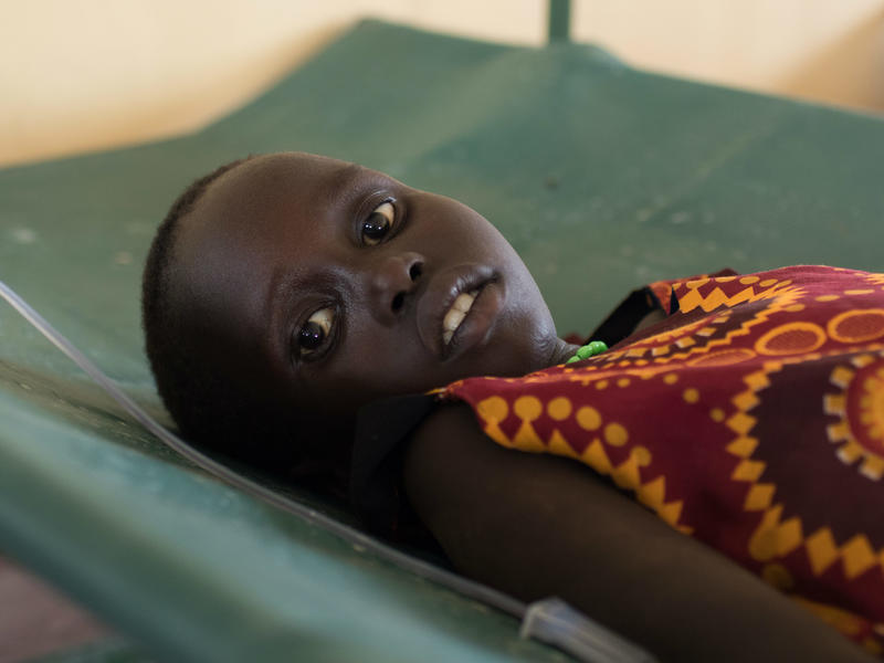 A young girl undergoing treatment for cholera lies on a cot, hooked up to an intravenous drip.