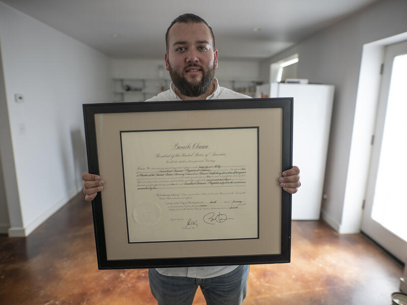 Suamhirs holds a certificate honoring his work on the U.S. Advisory Council on Human Trafficking.