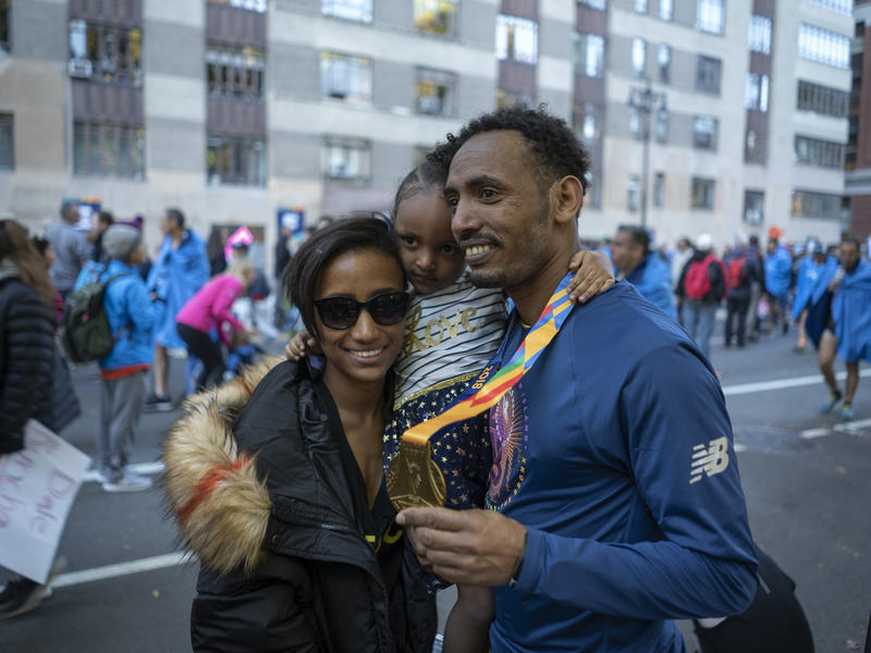 Tolassa Elemaa and his wife Bikiltu hold their daughter in Manhattan after the 2018 NYC Marathon