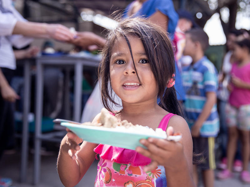 A Venezuelan girl holds a plate of food in Cúcuta, Colombia.