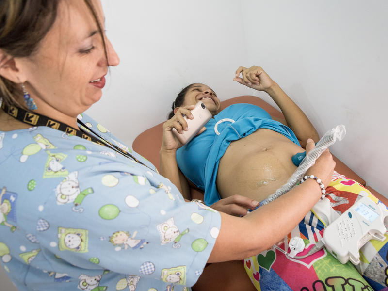 An IRC health worker examines a pregnant woman in an IRC clinic in Cucuta, Colombia