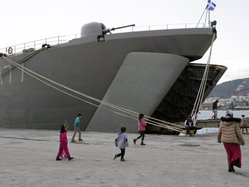 Refugees walk on a dock next to a Greek Navy ship on the Island of Lesbos