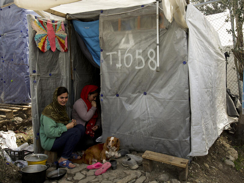 Parasi, a woman who came to Lesvos from Afghanistan, and a friend, sit outside their shelter with their dog Rex.