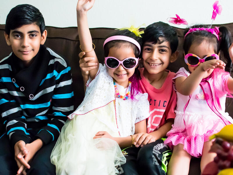 Syrian children resettled in San Diego pose for a silly photo on their couch while playing dress-up.