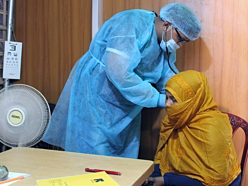 Dr. Sayed Muhaiminur Rahman uses a stethoscope to listen to Sakera's lungs at the IRC primary health care center.