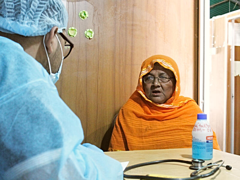 At the IRC health center in Cox's Bazar, Dr. Muhaiminur speaks with Ambia, a 60-year-old refugee