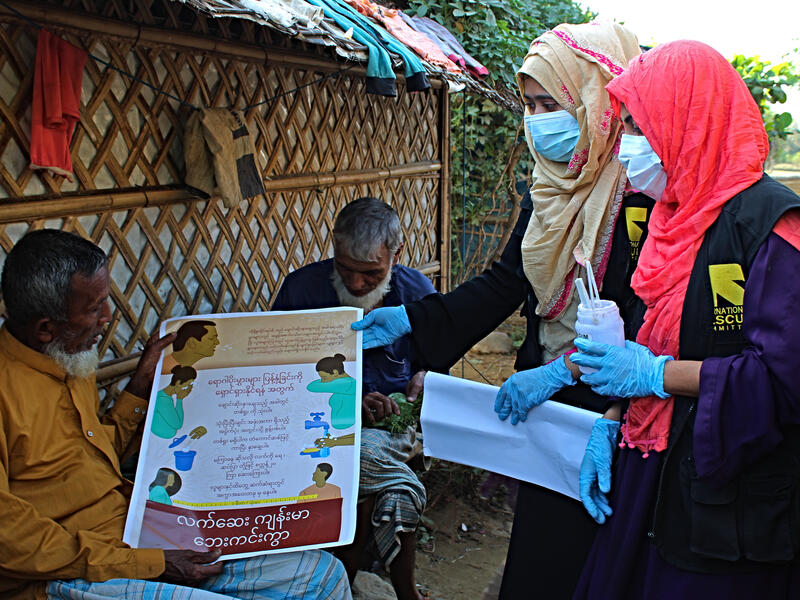 Two women who are IRC community health volunteers wear masks as they distribute information about the coronavirus to two men in the Cox's Bazar refugee camp