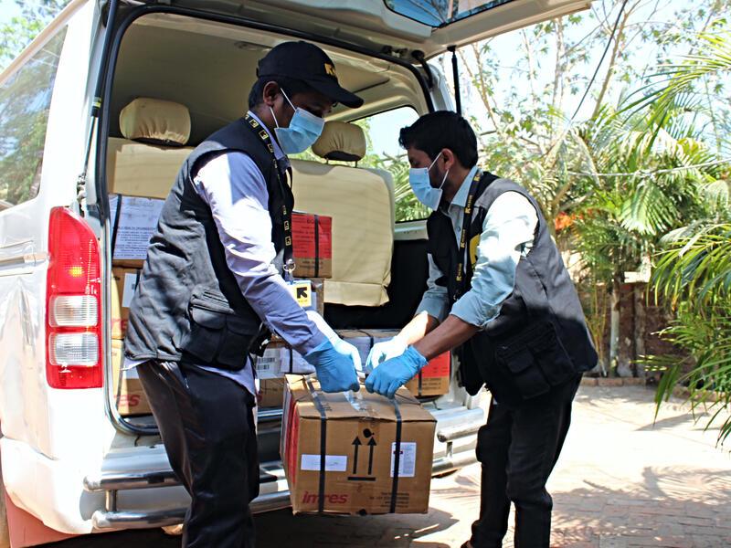 IRC staff unloads coronavirus prevention equipment from a truck