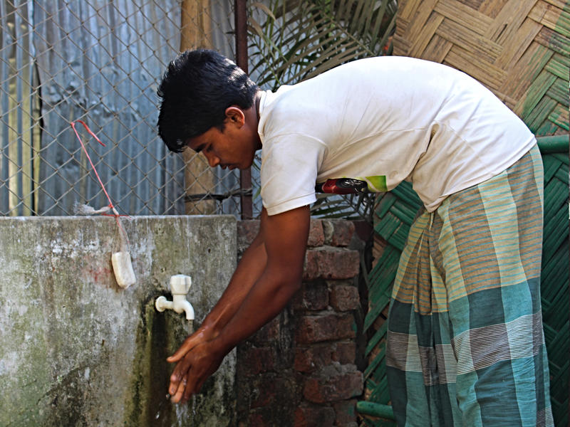 A young refugee bends over to wash his hands under an outdoor tap in the Cox's Bazar refugee camp.
