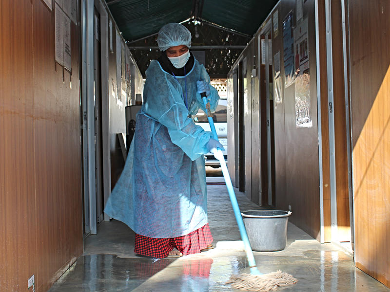 A health worker mops the floors as she disinfects an IRC 24-hour health facility in Cox's Bazar refugee camp