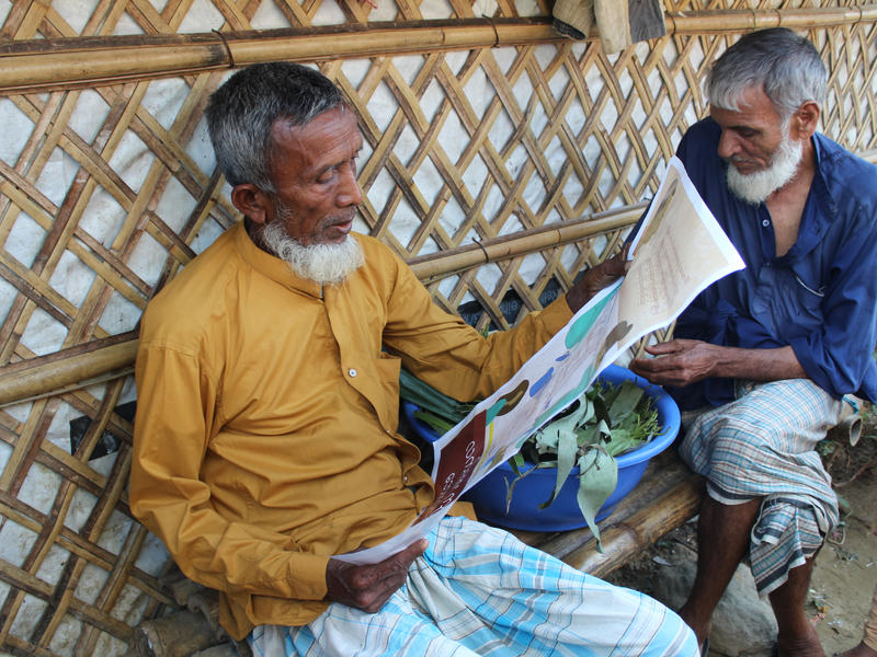 Two elderly men sit reading coronavirus information from the IRC in the Cox's Bazar refugee camp