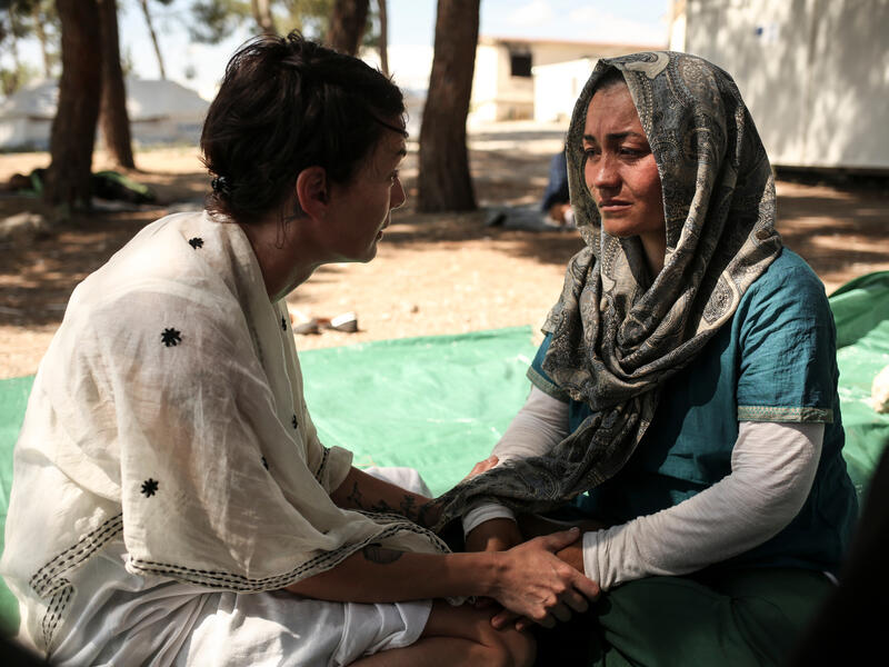 Lena Headey holds hands as she sits and speaks with a woman who is now a refugee from Afghanistan