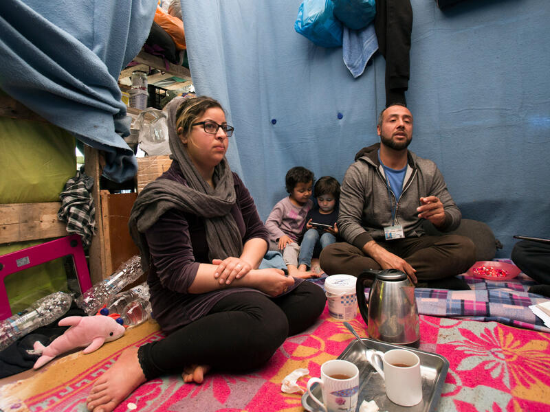 A family sits on the ground in a tent in Moria refugee camp on the island of Lesbos in Greece