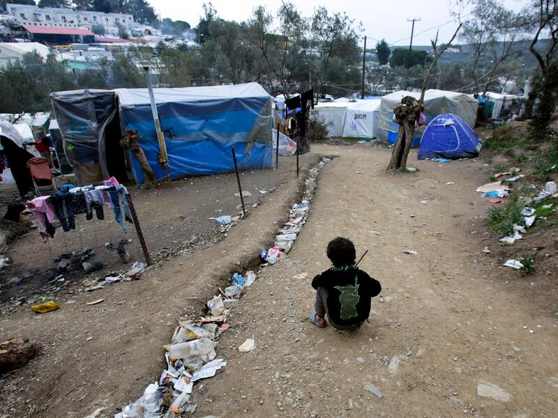 A child sis on the ground near tents in the Moria refugee camp on Lesbos, Greece