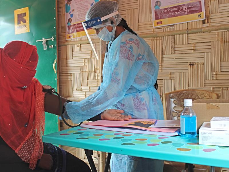 An IRC midwife wearing a mask, face shield and protective suit takes the blood pressure of a patient with a veil covering her face as a precaution during the coronavirus pandemic.