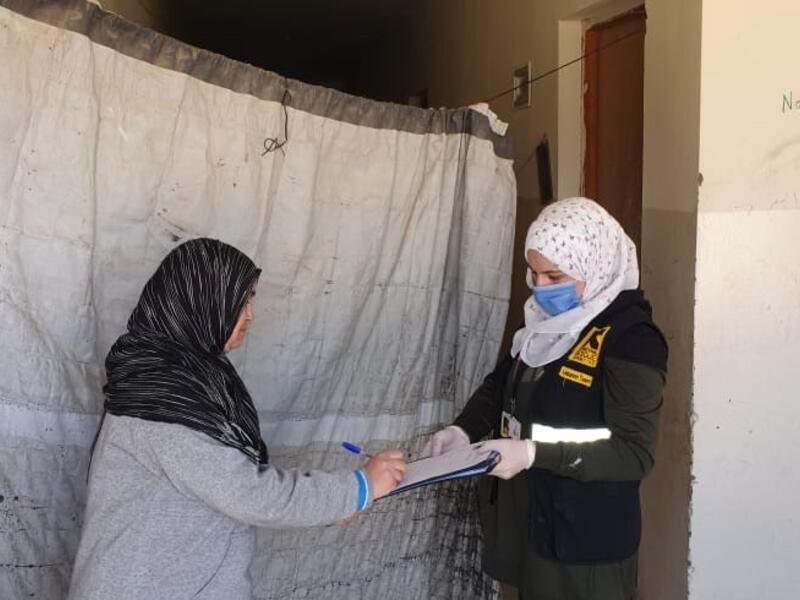 An IRC aid worker wearing a mask provides emergecy cash assistance to a woman in Bekaa, Lebanon.