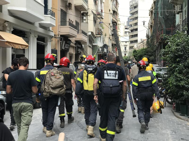 A group of Beirut firefighters responding to the explosion walk down a street
